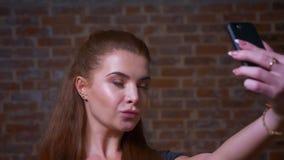 El primer caucásico bonito de la mujer del jengibre está enviando besos y está soplando en la cámara, hablando el selfie que mira almacen de metraje de vídeo