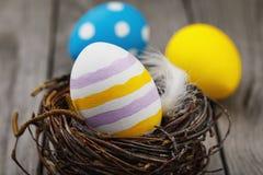El primer coloreado del huevo de Pascua en una jerarquía del abedul ramifica Fotos de archivo libres de regalías