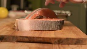 El primer cortó las rebanadas de color salmón de pescados dietéticos rojos en una tabla de cortar de madera Cocina casera Aliment almacen de video
