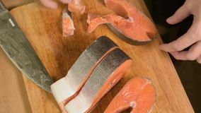 El primer cortó las rebanadas de color salmón de pescados dietéticos rojos en una tabla de cortar de madera Cocina casera Aliment almacen de metraje de vídeo