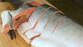 El primer cortó las rebanadas de color salmón de pescados dietéticos rojos en una tabla de cortar de madera Cocina casera Aliment metrajes