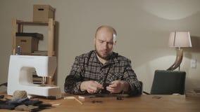 El primer crea la forma de un lazo de mariposa hecho de lanas Funcionamiento apuesto del hombre joven como un sastre y a con almacen de metraje de vídeo