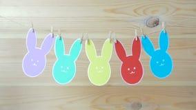 El primer de conejos y del papel de papel coloridos eggs marcos de la silueta contra fondo de la lona metrajes