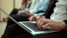 El primer de hombres da el mensaje de texto que mecanografía en el ordenador portátil, el estudiante joven que se sienta en las c almacen de metraje de vídeo