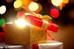 El primer de la caja de regalo abierta de la Navidad en brillar intensamente enciende el fondo Fotos de archivo
