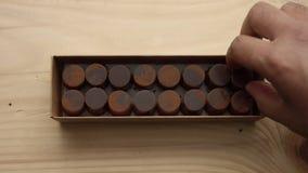 El primer de la caja del caramelo de chocolate y un ` s del hombre dan cogido de él almacen de metraje de vídeo