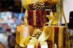 El primer de la estrella de oro y de los regalos de la Navidad llenados para arriba en pila empañó - el foco selectivo Imagen de archivo