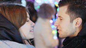 El primer de la fecha con un par hermoso bajo nevadas, hombre da flores y un regalo a una mujer por Año Nuevo metrajes