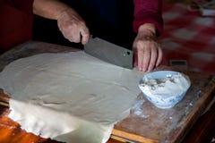 El primer de la mano amasa la pasta en un tablero de madera Prepare las crepes y las bolas de masa hervida de la harina foto de archivo