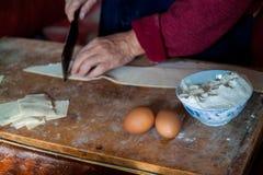 El primer de la mano amasa la pasta en un tablero de madera Prepare las crepes y las bolas de masa hervida de la harina fotografía de archivo libre de regalías
