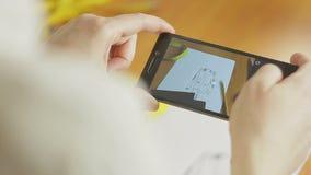 El primer de la mano del diseñador de moda que fotografía en el smartphone viste bosquejos en el taller almacen de metraje de vídeo