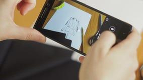 El primer de la mano del diseñador de moda que fotografía en el smartphone viste bosquejos en el taller metrajes