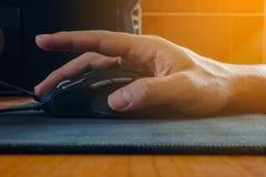 El primer de la mano del hombre que hace clic el ratón del ordenador y la llamarada se encienden Imagen de archivo