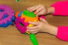 El primer de la mano del ` s del niño que toma el mosaico brillante parte aprendiendo colores en casa Niño pequeño en una camisa  foto de archivo libre de regalías
