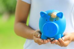 El primer de la mano de la mujer que sostiene la hucha azul atada al yeso en la cabeza, ahorra el dinero para el seguro médico y  fotos de archivo