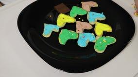 El primer de la mano de una muchacha, niño, asperjando las galletas deliciosas del caramelo dulce dobló bajo la forma de árbol de metrajes