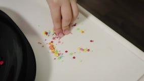 El primer de la mano de una muchacha, niño, asperjando las galletas deliciosas del caramelo dulce dobló bajo la forma de árbol de almacen de metraje de vídeo