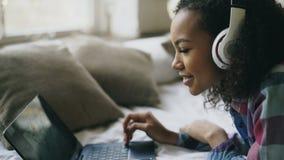 El primer de la muchacha afroamericana escucha la música mientras que mira las fotos en línea en el ordenador portátil que miente Fotografía de archivo