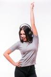 El primer de la muchacha caucásica morena feliz escucha baile la música con los auriculares fotos de archivo