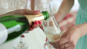 El primer de la muchacha vertió el champán en los vidrios