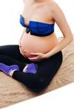 El primer de la mujer embarazada con entrega la panza en el fondo blanco Vientre hermoso de embarazada atractivo joven Foto de archivo