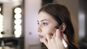 El primer de la mujer morena que aplica el cosmético en los pómulos con a compone el cepillo La muchacha en el maquillaje del sal metrajes