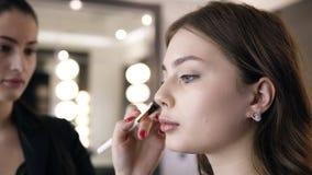 El primer de la mujer morena que aplica el cosmético en los pómulos con a compone el cepillo La muchacha en el maquillaje del sal almacen de video