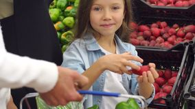 El primer de la niña compra el rábano fresco con sus padres en el supermercado almacen de video