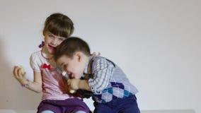 El primer de la niña y el muchacho comen manzanas y la lupa del juego metrajes