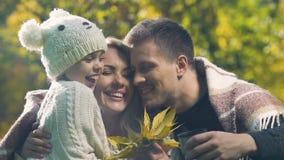 El primer de la pareja que habla en el parque, hija da las hojas de otoño, familia feliz metrajes