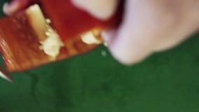 El primer de la pimienta roja de la paprika está consiguiendo el corte con el cuchillo en la tabla de cocina verde metrajes