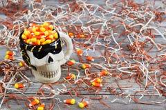 El primer de la taza esquelética asustadiza del cráneo de Halloween llenó del caramelo Imágenes de archivo libres de regalías