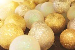 El primer de las bolas de la Navidad del oro y el abeto ramifican en piso con la luz caliente Imagenes de archivo