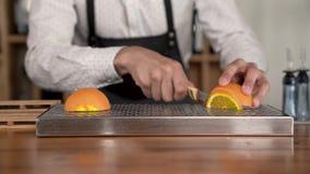 El primer de las manos del camarero corta la fruta anaranjada en el contador de la barra almacen de video