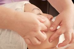 El primer de las manos del cosmetólogo hace el masaje de la barbilla a la mujer El masajista presiona sus fingeres en la cara fem fotografía de archivo libre de regalías