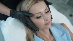 El primer de las manos del doctor en guantes negros muestra áreas o la zona del tratamiento para el procedimiento cosmético, stea almacen de video