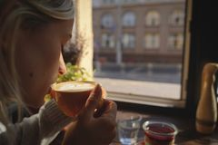 El primer de las manos del ` s de la mujer con una taza de torta de café, los rayos del ` s del sol brilla a través de una ventan fotografía de archivo