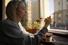 El primer de las manos del ` s de la mujer con una taza de torta de café, los rayos del ` s del sol brilla a través de una ventan imagenes de archivo