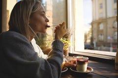 El primer de las manos del ` s de la mujer con una taza de torta de café, los rayos del ` s del sol brilla a través de una ventan foto de archivo libre de regalías