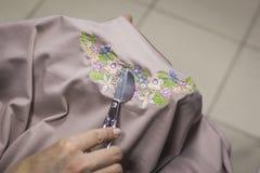 El primer de las manos del trabajador de mujer pone fin a los extremos flojos de los hilos de la ropa con las tijeras agudas foto de archivo