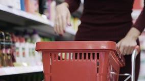 El primer de las manos de la mujer puso productos en la carretilla en supermercado metrajes
