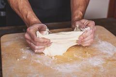 El primer de las manos masculinas amasa la pasta para la pizza hecha en casa, los problemas de cocinar, cocinero incompetente fotos de archivo