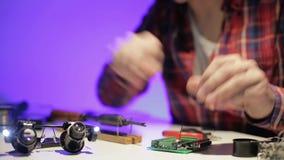 El primer de las manos masculinas soldó el alambre a la placa de circuito impresa almacen de metraje de vídeo
