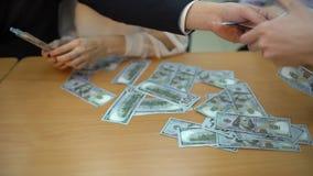 El primer de las manos de un equipo del negocio toma cientos billetes de dólar en una tabla Primer una gran cantidad de dinero 4  metrajes