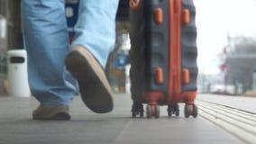 El primer de las piernas va a lo largo de la plataforma del ferrocarril, una maleta se está llevando cerca Transporte y metrajes