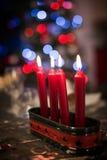 El primer de las velas rojas del advenimiento de la Navidad en una tabla, bokeh se enciende Fotografía de archivo libre de regalías