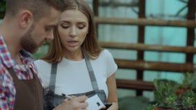 El primer de los floristas jovenes de los pares trabaja en centro de jardinería Flores cheking y mujer del hombre atractivo que u almacen de metraje de vídeo