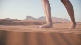 El primer de los pies del ` s de las mujeres se hunde en la arena Caminata en el desierto almacen de metraje de vídeo