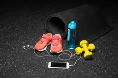 El primer de los zapatos del entrenamiento, de la estera de goma, de pesas de gimnasia, de la botella azul y del teléfono en un n imagenes de archivo