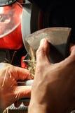 El primer de manos afila el hacha que afila la máquina Fotos de archivo